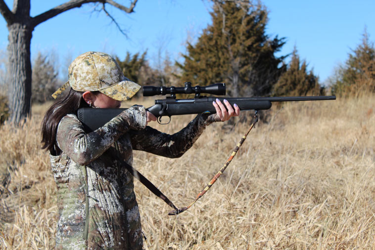 Campfire Collective Hunting Ambassador Chloe Annalcazar dressed in campuflage, taking aim with a bolt action rifle.