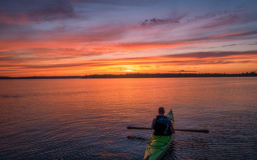 Campfire Collective Kayaking Ambassador Gordon Pusnik in his kayak on Kennisis Lake at sunset.