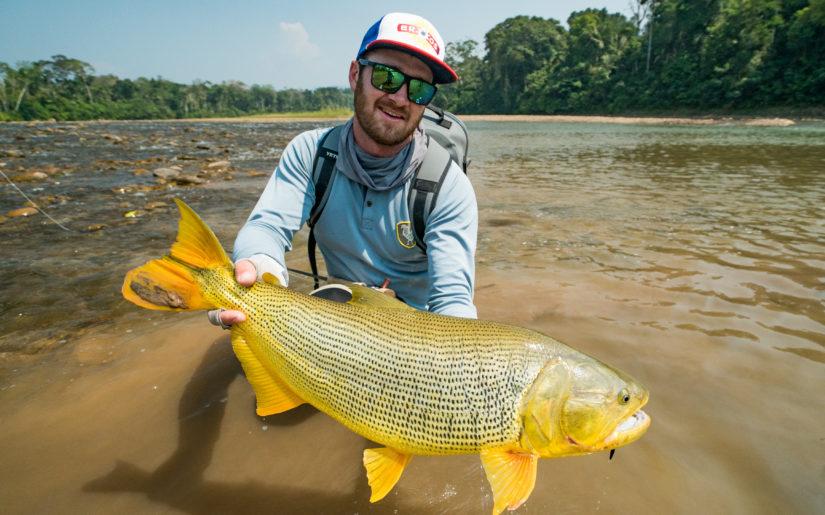 Campfire Collective Fishing Ambassador Christiaan Pretorius holding a Golden Dorado on a fishing trip Bolivia.