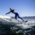 Wakesurfer wearing cold-water wetsuit, surfing the wake behind a boat.