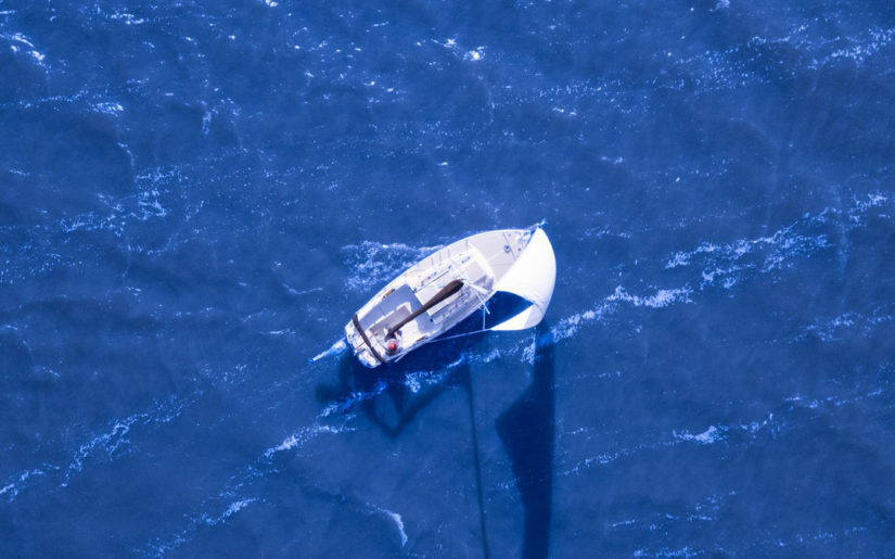 Aerial view of sailboat racing through blue waters.