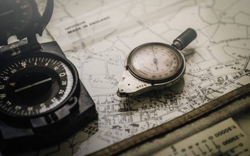 Close-up shot of a boating trip being planned using nuatical charts and compass.