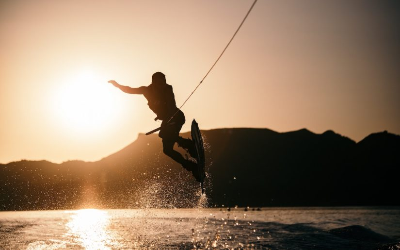 Wakeboarder performing a trick over the wake behind a boat.