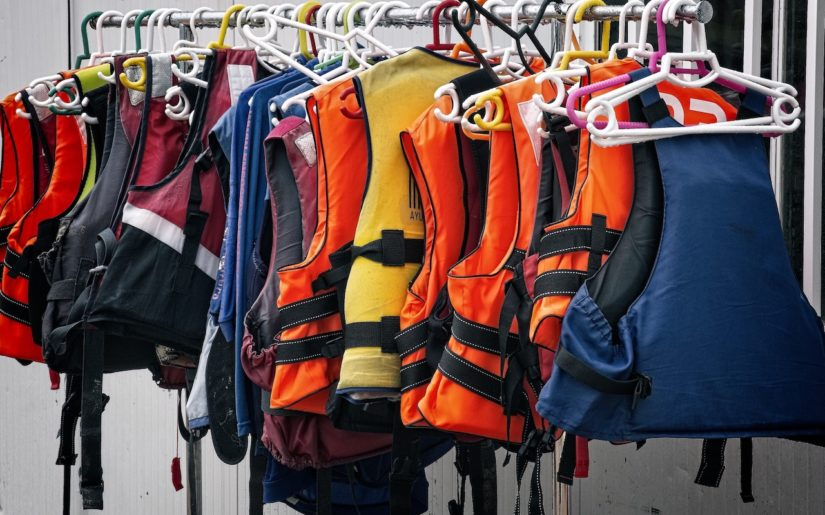 Colourful lifejackets hangings on a rack.